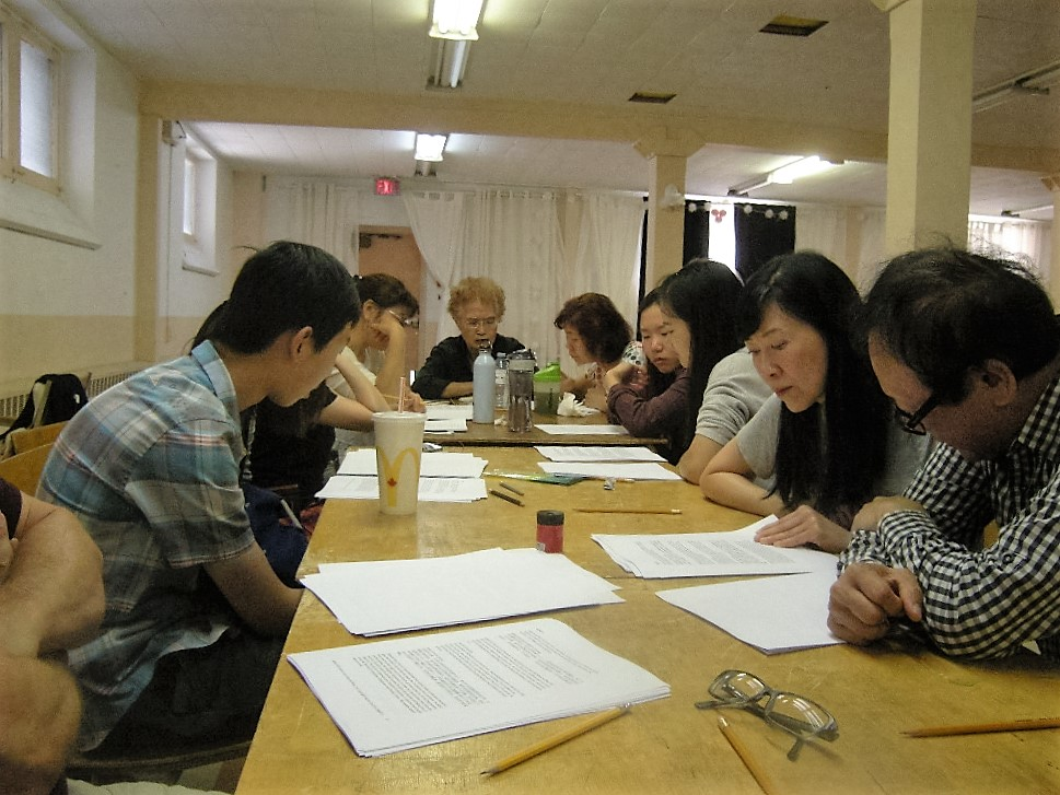 A group of people reading documents at a table.
