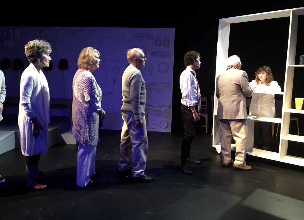"""A group of people are lined up single file during a performance of """"Shelf Life"""". At the front of the line is a pharmacist handing out medication."""