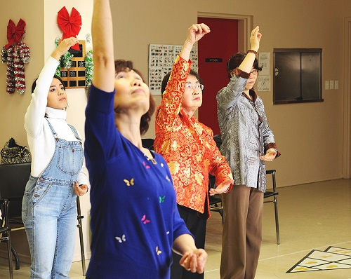 "Four people standing with their right arms reaching up during a workshop for ""Spring Moon."""