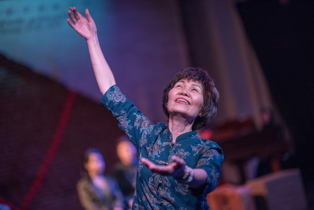 An older adult is on a stage, smiling, with their left arm stretched up and their right beckoning forward.