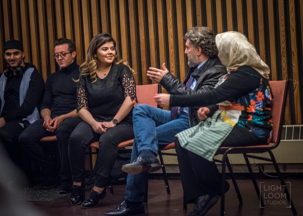 """A photo of five people sitting on chairs during """"Art for Integration"""". One person is looking at the person to their right and is holding their arm out, in the middle of speaking."""